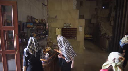 conservative : KUTAISI. GEORGIA - OCT 2018: Women purchase incense at a shop in the Bagrati Cathedral