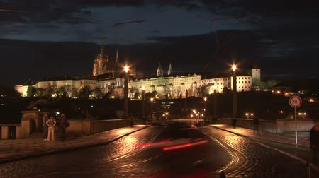 Прага : Twilight panorama of Prague castle with walking people and traffic on the bridge. Time lapse. Стоковые видеозаписи