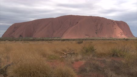 rocks red : Uluru - Ayers Rock. Aboriginal sacred place. UNESO world heritage. Sunrise sun is color painting red sandstone rock. Time lapse. PR available - image approved for commercial use by Park authorities.