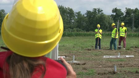 field measurements : Geodesist with workers are adjusting pillar in cement for solar power plant construction. Stock Footage
