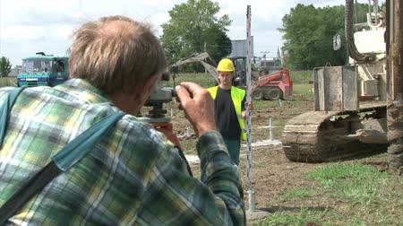 field measurements : Geodesist and worker are adjusting pillar in cement for solar power plant construction. Stock Footage