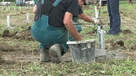 field measurements : Workers are tuning the right pillar possition in cement for solar power plant construction.
