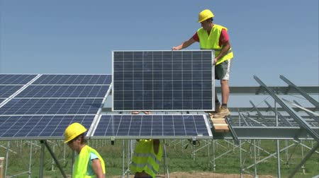 panel buildings : Workers are mounting panels on solar powerplant construction.