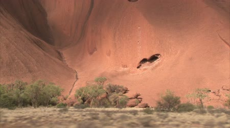 authorities : PR available - image approved for commercial use by Park authorities. Uluru - Ayers Rock. Aboriginal sacred place. UNESO world heritage. Sun is color painting red sandstone rock. Dolly left to right.