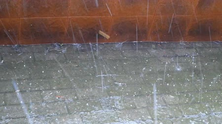 влажность : Rain and hail with increasing intensity falling on the walkway near the fence Стоковые видеозаписи