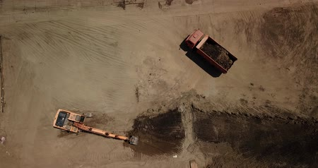 wheel loader : Aerial footage of excavator pours sand into the truck. On the construction site top view. Shooting from the drone Stock Footage