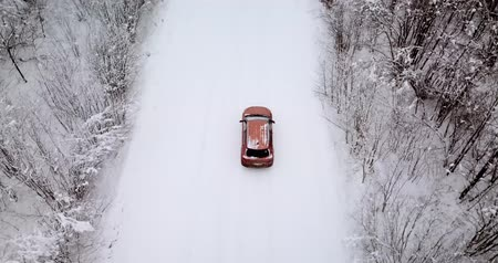 Aerial view of a snowy forest and road with a car in the winter.