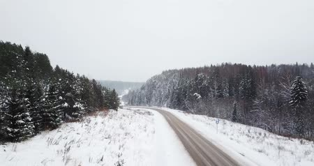 Aerial view fly over the highway winter road among the snowy forest. Stock Footage
