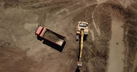 Aerial view of excavator pours sand into the truck.