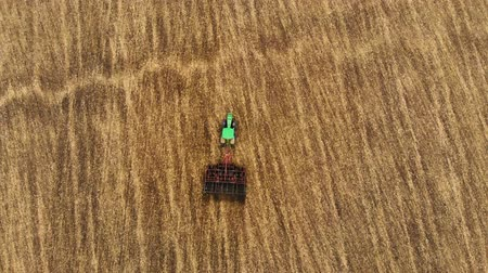 Aerial view of tractor sowing wheat, cultivating land in extreme close up slow motion. Stock Footage