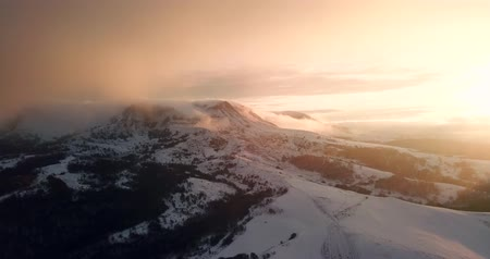 Aerial Drone Flight Over Mountain Range Through Clouds At Sunset