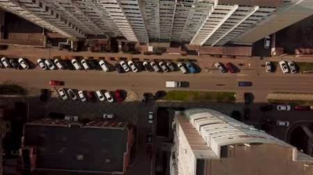 вниз : Top down view of fly between cityscapes in downtown with traffic.