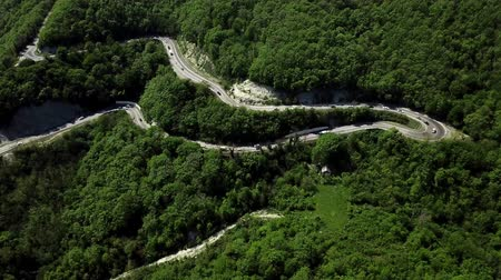 serpentine : Aerial view of a curved winding road with cars passing Stock Footage