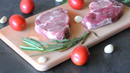 вырезка : Raw pork steaks with rosemary, garlic and tomatoes on a wooden cutting board Стоковые видеозаписи