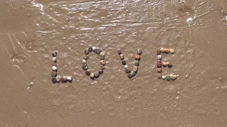 apagar : Love word writing with small stones on sand beach ground