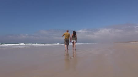 boso : woman and man couple walking on sand beach next to Zahara village at Cadiz Spain  Wideo