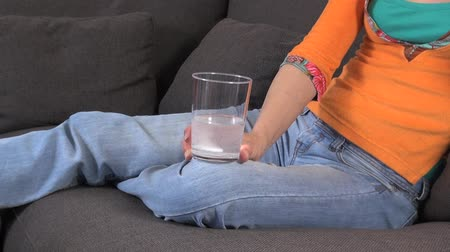 efervescente : woman on a sofa with effervescent medicine on a glass  Vídeos