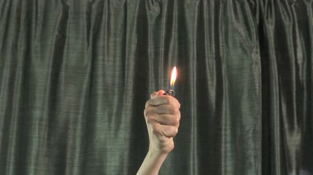 çakmak : woman hands moving fired lighter with green curtain at background