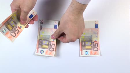 wealth : man hand distributing 50 euros banknotes on blue background