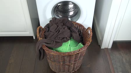 çamaşırhane : clothes falling in wicker basket next to white washing machine  Stok Video