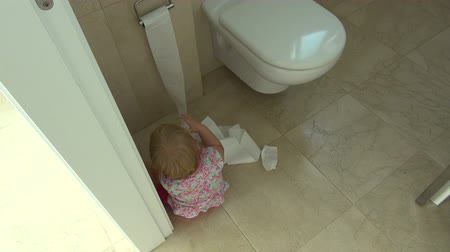 уборная : baby one year old barefoot with pink shorts playing with toilet paper at bathroom Стоковые видеозаписи