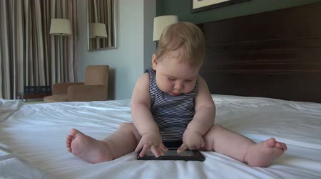 baby chubby : baby nine month old playing with smartphone on white bed sheet Stock Footage