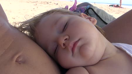 кнопка : thirteen month old baby face sleeping on moms belly at the beach