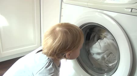 çamaşırhane : baby fourteen month old looking at door of white washing machine running