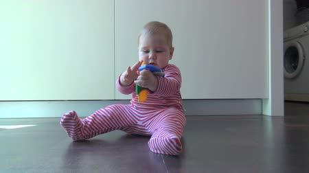 baby chubby : nine month old baby lying in kitchen floor playing with color plastic keys Stock Footage