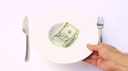çatal : man hand serving soup plate with dollar money five banknote on white background between silver fork and knife