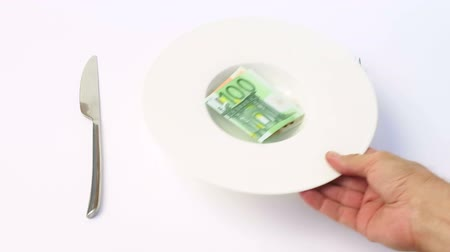 çatal : man hand serving soup plate with Euro money five banknote on white background between silver fork and knife