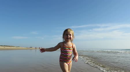 pursue : slow motion two years age blonde baby with swimsuit colored stripes walking, running and playing with water trying to catch the camera on golden sand beach seaside ocean Stock Footage