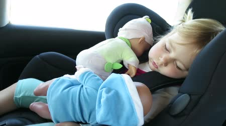 boneca : tender scene of blonde caucasian baby face two years old age sitting in black baby car seat sleeping with dolls in her arms, vehicle is driving Vídeos