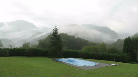 брезент : landscape of green meadow with swimming pool closed and covered with blue tarp in winter rounded by mountains with fog and rain and clouds running in Nature in Asturias Spain Europe