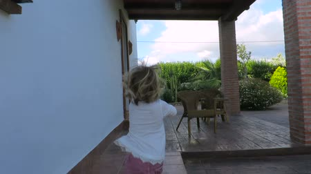 pursue : slow motion back shooting following two years age blonde baby girl with white shirt in exterior garden running to porch and door house