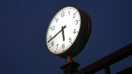 minuta : View on a train station clock at night as the seconds are passing.