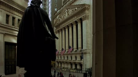 NEW YORK CITY, USA - OCT 30, 2018: Walkway view Stock Exchange and Washington Statue in Wall Street with skyscrapers as the famous financial district in downtown Manhattan.