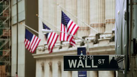 Wall Street road sign and New York Stock Exchange out of focus in downtown Manhattan.