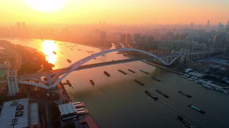 Lupu Bridge with cargo ship in Huangpu River at sunset aerial drone view in China