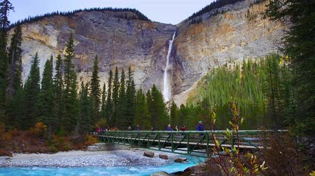 np : Yoho NP, Canada - September 26, 2018: Takkakaw Falls with bridge and tourists.  Takkakaw Falls is one of the famous travel attractions in in Yoho National Park.