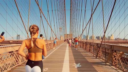 ブルックリン : New York City - Sept 28, 2018: People walk on Brooklyn Bridge in - sunny day. New York City  is the most populous city in the United States. 動画素材