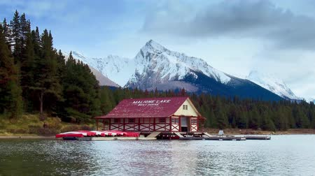 jasper : Jasper, Canada - September 23, 2018: Maligne Lake boat house with snow mountain and lake timelapse panning view. Maligne Lake is one of the famous travel attractions in Jasper National Park.