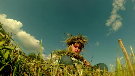 çelenk : little girl weaves a wreath of grass on the field near the river under the blue sky summer