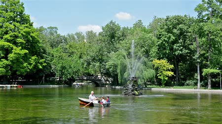 bitki : BUCHAREST, ROMANIA - MAY 26: People Rowing Boat In The Cismigiu Gardens on May 26, 2014 in Bucharest, Romania. It is a public park (built in 1847) downtown Bucharest, spanning areas on all sides of an artificial lake. Stok Video