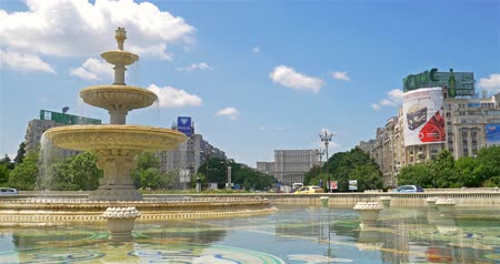 traffic bucharest : BUCHAREST, ROMANIA - JUNE 15, 2016: Union Square Fountain And House Of The People Or Parliament Palace (Casa Poporului) View From Union Boulevard (Bulevardul Unirii) In Downtown Bucharest.