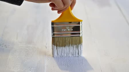 Painter Is Painting And Varnishing Wood Boards In White Color With Paintbrush
