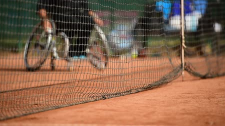 rokkant : Wheelchair tennis player is seen behind the tennis net on a clay court Stock mozgókép