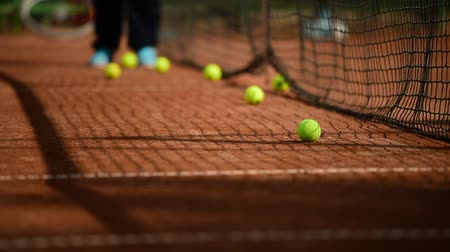 tennis stadium : Ball boy retrieves tennis balls from a clay tennis court during practice game Stock Footage