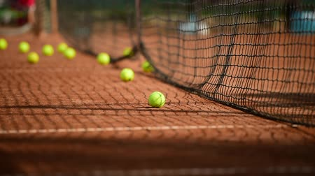 tennis stadium : Tennis balls hitting the tennis net during practice game on a clay court