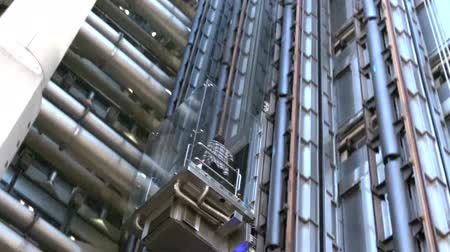 biztosítás : LONDON - MAY 13 2015:Businesswoman in a lift of Lloyds Building.Its Lloyds insurance headquarter also knowen as the inside-out building as its lifts, stairs and most of the piping exposed outside.